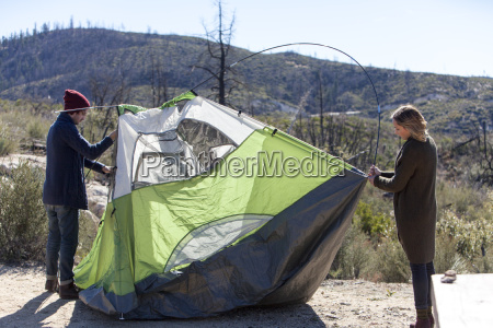 young couple erecting tent in rural