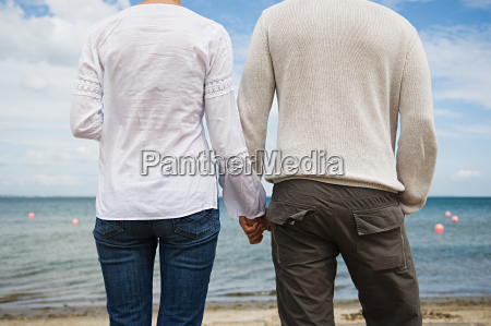 couple holding hands on the beach
