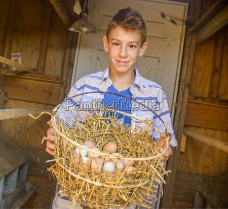 portrait of boy carrying basket of