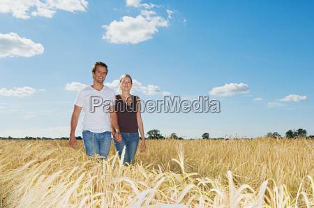 couple walking in a field of