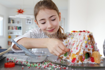 girl at kitchen counter decorating ginger