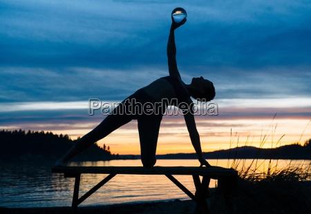 woman practising yoga by lake at