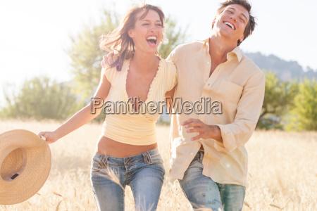 happy romantic couple strolling in field
