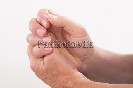person pressing his palm with thumb