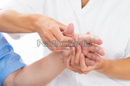 person receiving palm massage by physiotherapist