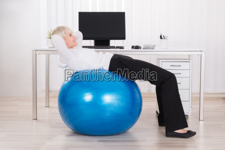 businesswoman doing workout with fitness ball