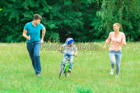 parents running with their son riding