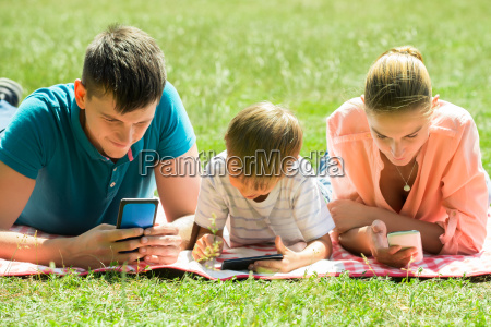 family laying down in the park