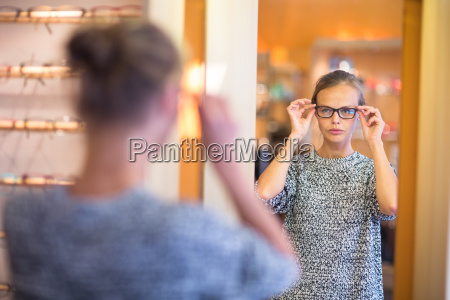 pretty young woman choosing new glasses