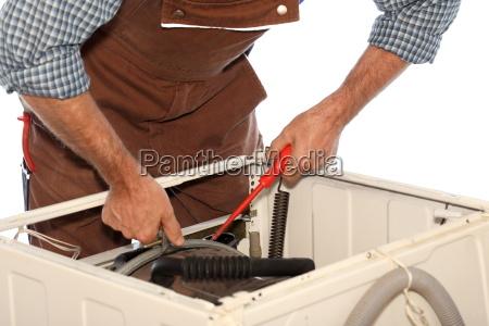 craftsman works on washing machine