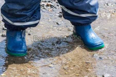 children legs in blue rubber boots