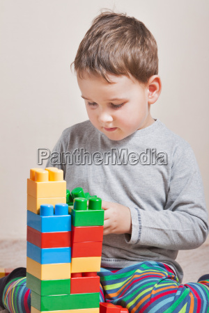 playing little boy with colored cubes