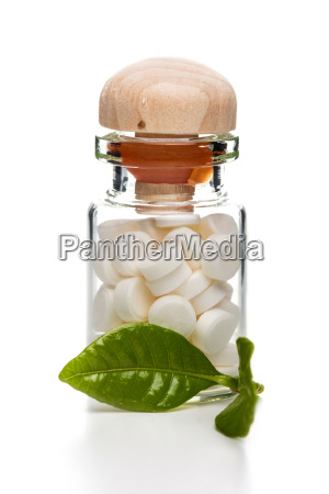 white pills in glass container with