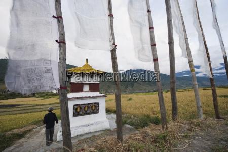 a man circumambulating a stupa with
