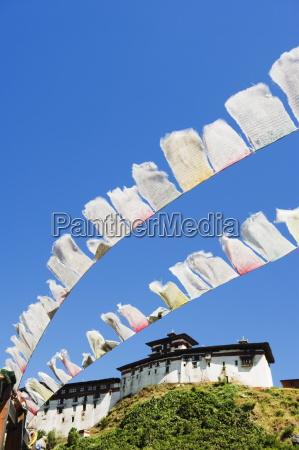prayer flags below wangdue phodrang dzong
