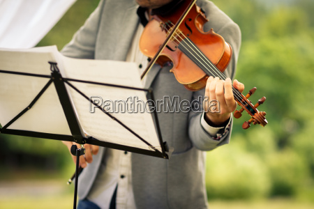 male violinist playing his instrument and
