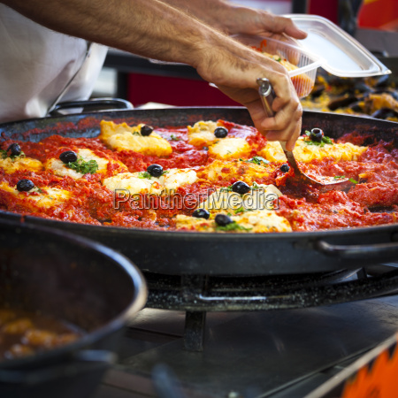 man cooks catalan cuisine in the