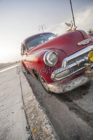 red car on the malacon havana
