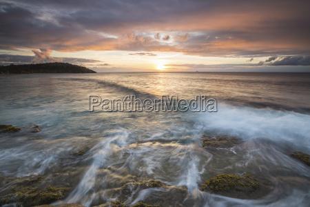 waves crash on cliffs under a