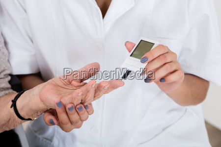 doctor holding patients finger checking sugar