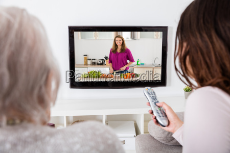 two women watching cooking show on