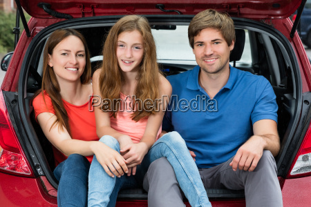 family sitting in trunk of their