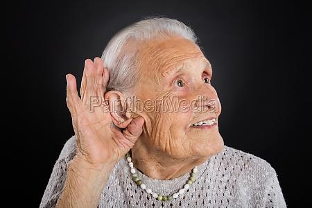 happy senior woman trying to hear