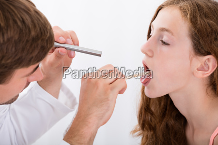 close-up, of, doctor, examining, girl's, throat - 19169895