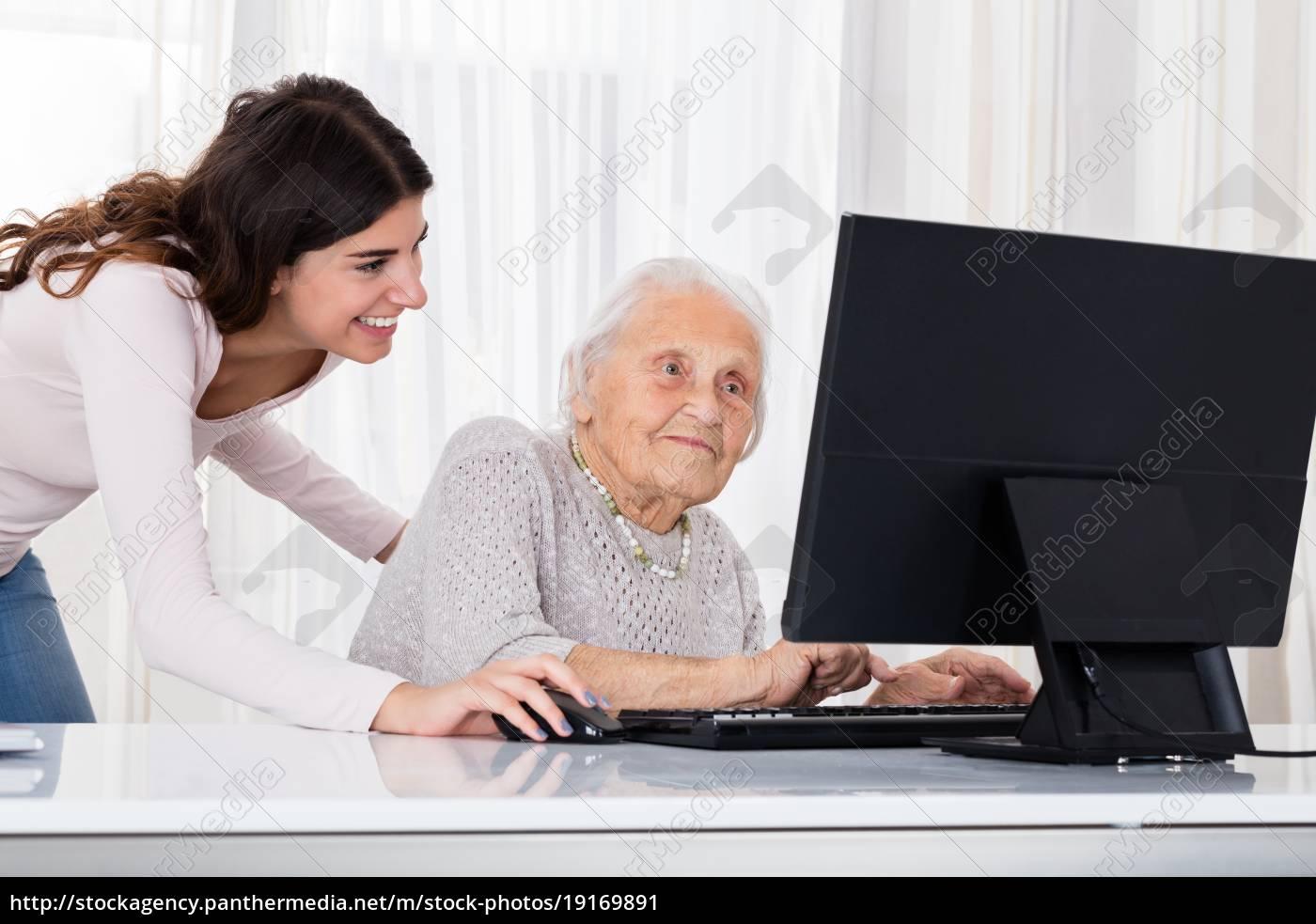 two, smiling, women, using, laptop - 19169891