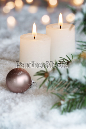 two christmas candles in the snow