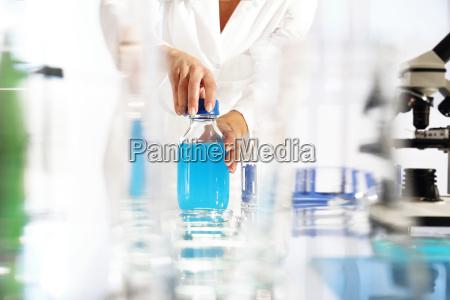 the chemist examines the sample under