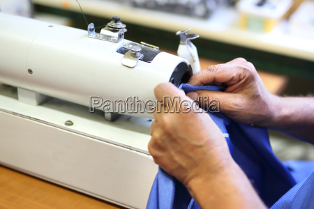 the seamstress sews up the trouser