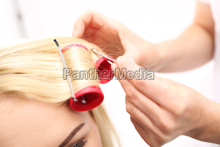 the hairdresser wraps the rolls and