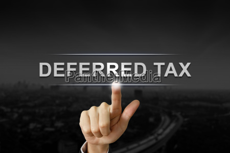 business hand pushing deferred tax button
