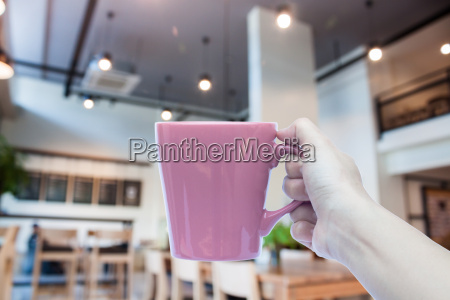 woman holding coffee cup with abstract