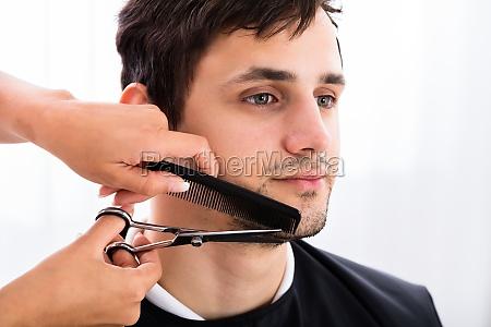 hairdresser shaping mans beard