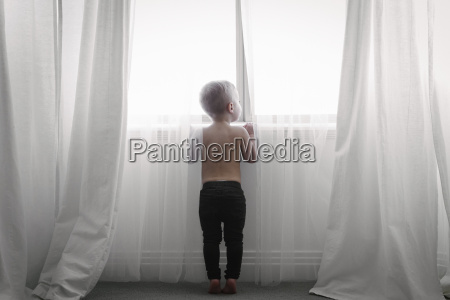 a child standing at a window