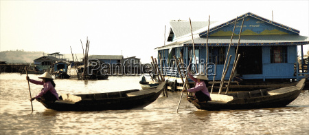 traditional women paddling boats across river
