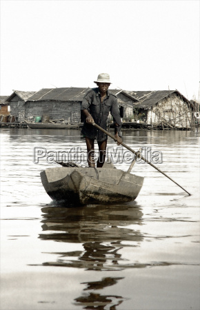 man standing on boat in river
