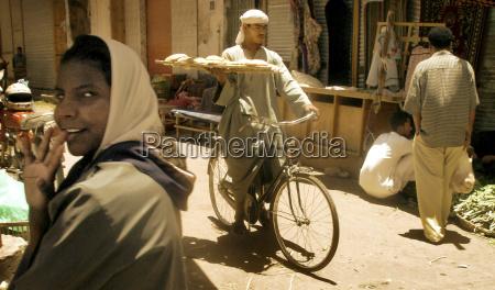 a baker cycling along carrying fresh
