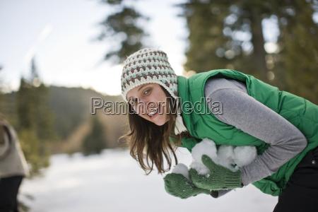 young woman making snowballs