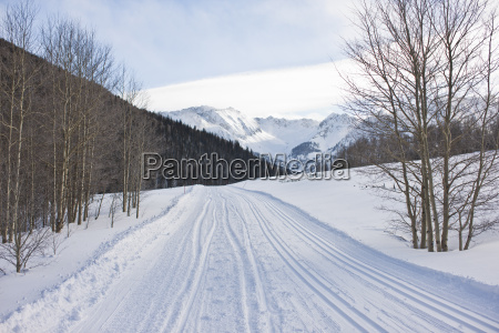 empty snowy road below a mountain