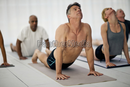 group of yoga class attendees stretch