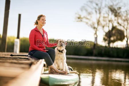 mid adult woman sitting on wharf