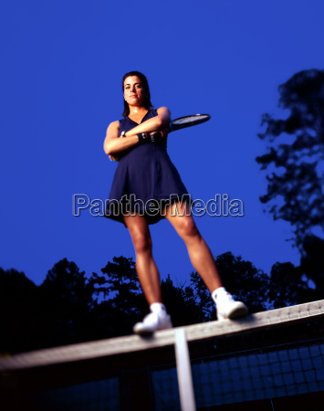 tennis player standing on net with