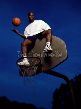 basketball player atop blackboard tossing ball