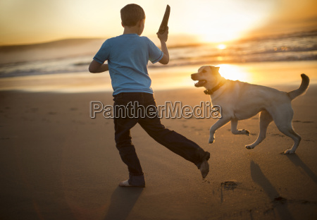 young boy playing fetch with a