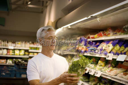 mature man holding up a lettuce