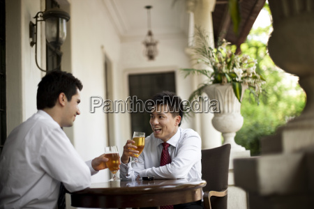 two smiling businessmen sharing a drink