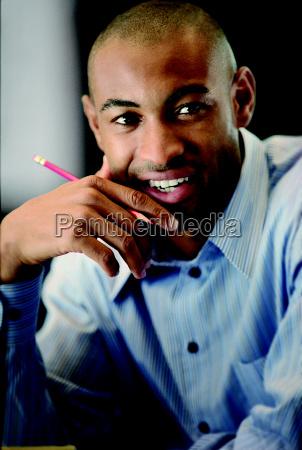businessman sits holding pencil